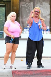 Dog the Bounty Hunter gives wife Beth a kiss as they make their way out of a couples tanning session in Los Angeles