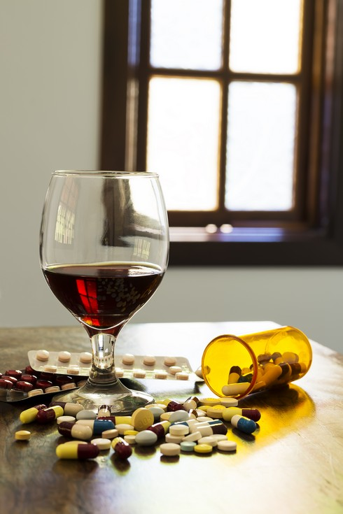 Wine glass, beside a large amount of capsules, pills and tablets falling out of the pot, with a blurred window in the background.