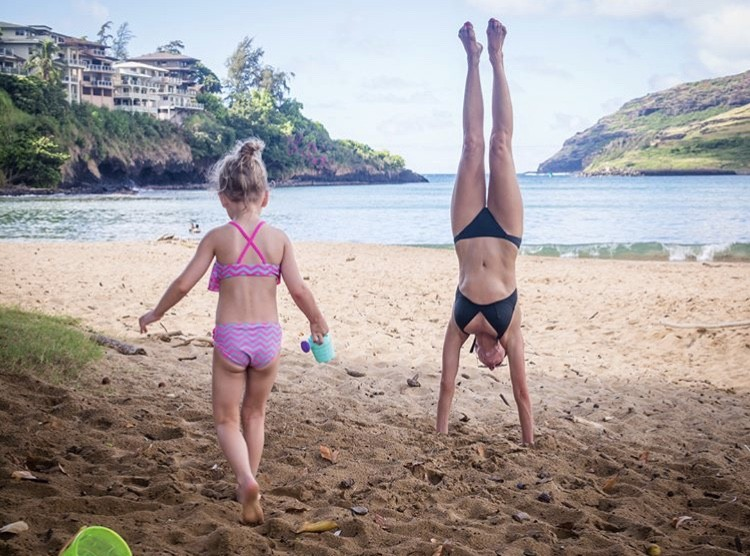Cary Doing A Handstand With Her Daughter